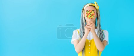 Photo for Panoramic shot of girl with dreadlocks covering face with lollipop isolated on turquoise - Royalty Free Image