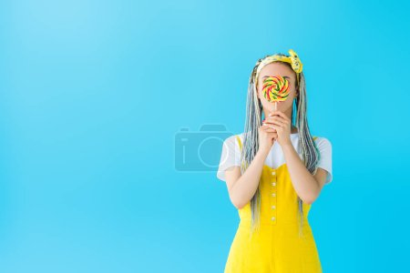 Photo for Girl with dreadlocks covering face with lollipop isolated on turquoise with copy space - Royalty Free Image
