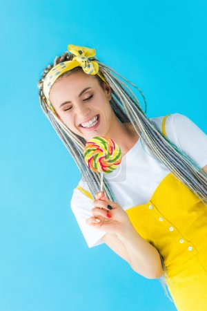 Photo for Smiling girl with dreadlocks holding lollipop isolated on turquoise - Royalty Free Image