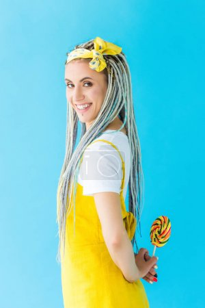 Photo for Smiling girl with dreadlocks looking at camera while holding lollipop isolated on turquoise - Royalty Free Image