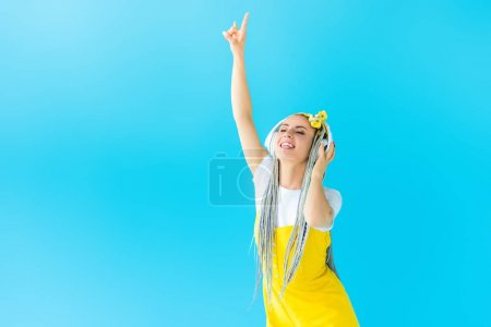 Photo for Girl with dreadlocks in headphones doing rock sign isolated on turquoise - Royalty Free Image