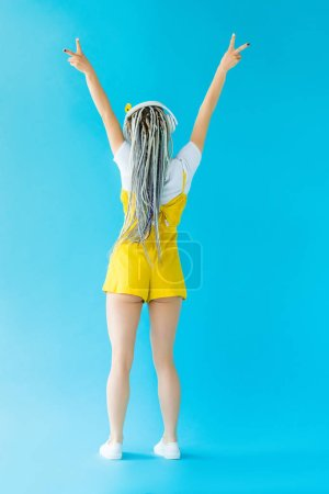 Photo for Back view of girl with dreadlocks in headphones showing peace signs on turquoise - Royalty Free Image