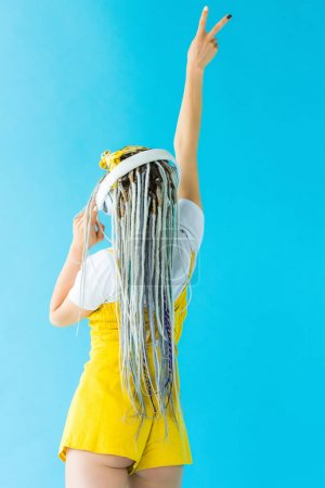 Photo pour Back view of girl with dreadlocks in headphones doing Peace Sign isolated on turquoise - image libre de droit