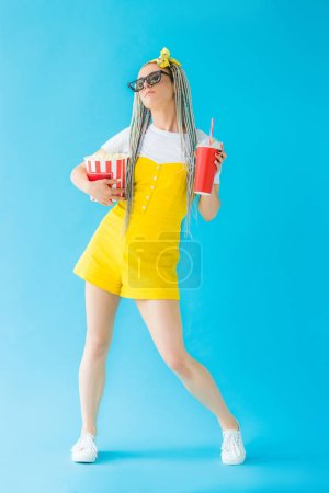 girl with dreadlocks in 3d glasses holding soda drink and popcorn on turquoise