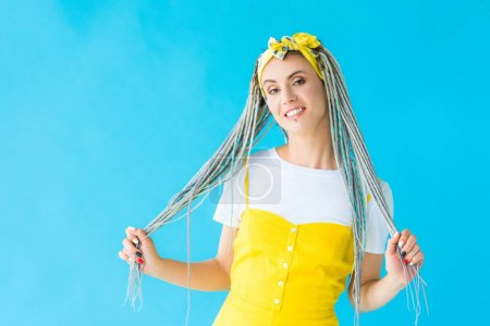 Photo pour Fille heureuse avec des cheveux de fixation de dreadlocks d'isolement sur le turquoise - image libre de droit