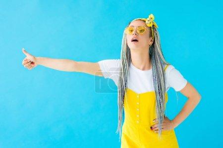 Photo pour Fille avec dreadlocks dans des lunettes de soleil montrant pouce vers le haut isolé sur turquoise - image libre de droit