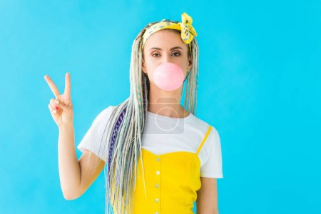 Photo pour Girl with dreadlocks blowing bubblegum and showing peace sign isolated on turquoise - image libre de droit