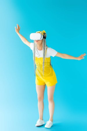 Photo for Girl with dreadlocks in Virtual reality headset gesturing on turquoise - Royalty Free Image