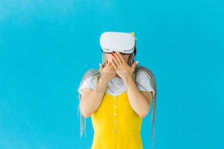 Photo for Girl with dreadlocks in virtual reality headset covering mouth isolated on turquoise - Royalty Free Image