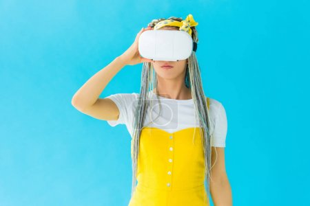 Photo for Girl with dreadlocks in virtual reality headset isolated on turquoise - Royalty Free Image