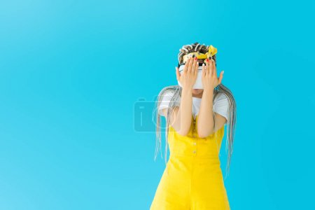 girl with dreadlocks in Virtual reality headset isolated on turquoise with copy space