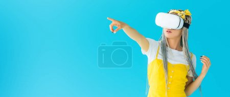 Photo for Panoramic shot of girl with dreadlocks in virtual reality headset pointing with finger isolated on turquoise - Royalty Free Image