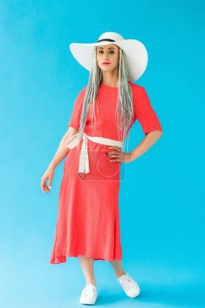 Photo pour Belle fille dans le chapeau et la robe posant sur le turquoise - image libre de droit
