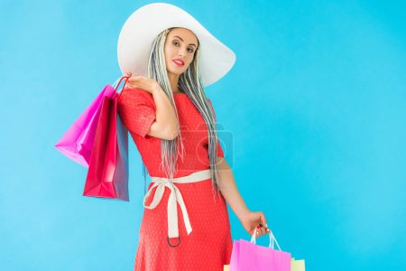 beautiful smiling fashionable girl with shopping bags isolated on turquoise