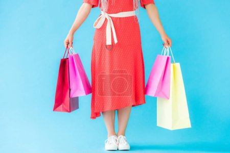 Photo for Cropped view of fashionable girl with shopping bags on turquoise - Royalty Free Image