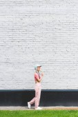 "Постер, картина, фотообои ""side view of girl in hat eating lollipop near brick wall"""