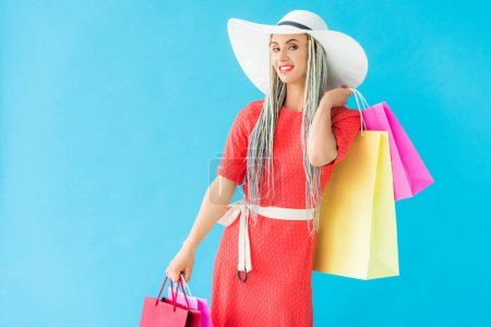 Photo for Beautiful smiling fashionable girl with shopping bags isolated on turquoise - Royalty Free Image