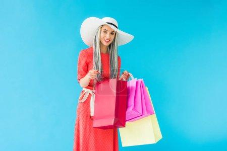 Photo pour Belle fille élégante avec des sacs à provisions isolés sur turquoise - image libre de droit