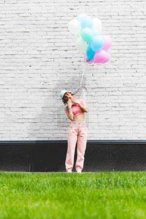 Photo pour Fille élégante avec des ballons décoratifs couvrant la bouche près du mur de briques - image libre de droit