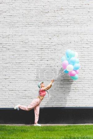 Photo pour Fille élégante posant avec des ballons décoratifs près du mur de briques - image libre de droit