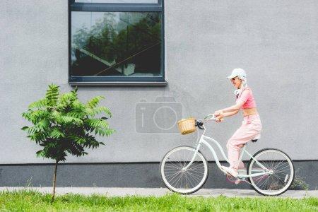 Photo pour Vélo élégant d'équitation de fille de sourire près du bâtiment - image libre de droit