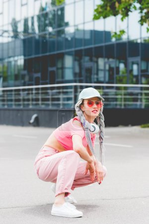 Photo for Stylish girl in sunglasses with headphones sitting and posing near building - Royalty Free Image