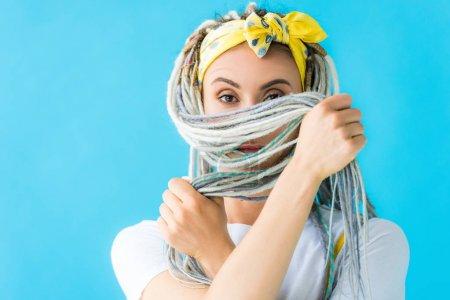 Mädchen mit Dreadlocks bedeckt Gesicht mit Haaren und blickt vereinzelt in die Kamera auf Türkis