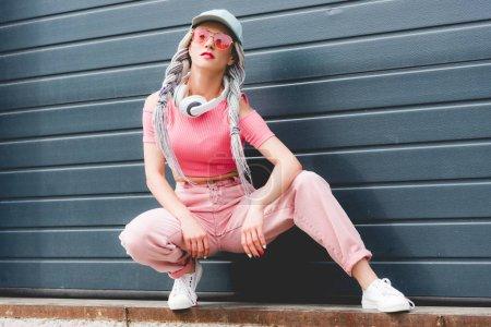 beautiful stylish girl with dreadlocks and headphones posing near wall