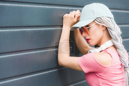 Photo for Fashionable girl with dreadlocks and headphones leaning on wall - Royalty Free Image