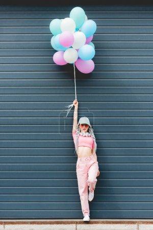 Foto de Stylish girl posing with decorative balloons near wall - Imagen libre de derechos