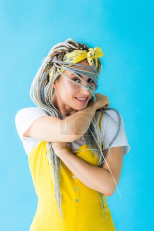 girl with dreadlocks covering face with hair and looking at camera isolated on turquois
