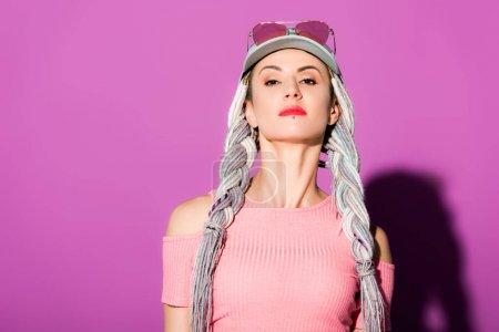 Photo pour Fille à la mode attirante avec des dreadlocks dans le chapeau posant sur le pourpre - image libre de droit