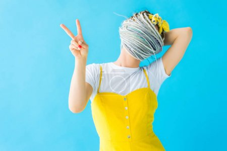 Photo for Girl with dreadlocks covering face with hair and showing peace sign isolated on turquoise - Royalty Free Image