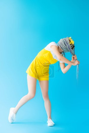 Photo for Girl with dreadlocks covering face with hair on turquoise with copy space - Royalty Free Image