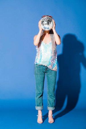 Photo pour Visage élégant de couverture de fille avec la bille de disco sur le bleu - image libre de droit