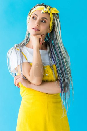 Photo for Thoughtful girl with dreadlocks propping chin with hand isolated on turquoise - Royalty Free Image