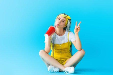 Photo pour Belle fille avec des dreadlocks se reposant, affichant le signe de paix et buvant le soude sur le turquoise - image libre de droit