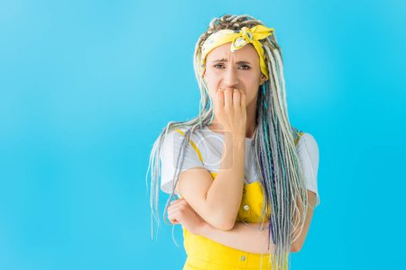 Photo for Scared girl with dreadlocks covering mouth isolated on turquoise - Royalty Free Image