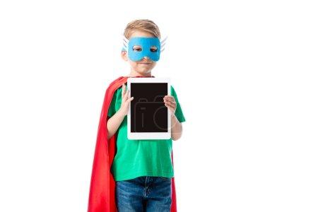 Photo pour Garçon préscolaire souriant en masque et manteau de héros tenant tablette numérique avec écran blanc isolé sur blanc - image libre de droit