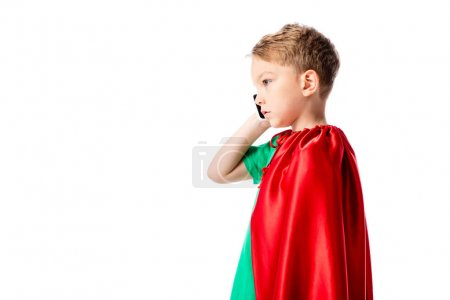 Photo for Side view of serious preschooler boy in red hero cloak talking on smartphone isolated on white - Royalty Free Image