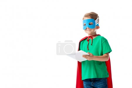 Photo for Smiling preschooler child in mask and red hero cloak using digital tablet isolated on white - Royalty Free Image