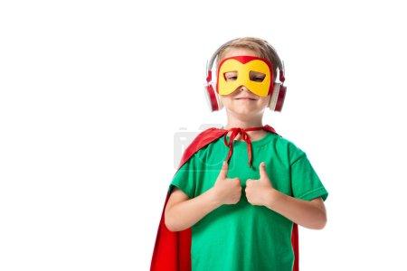 Photo pour Vue de face de l'enfant préscolaire souriant dans le masque et manteau héros rouge écouter de la musique dans les écouteurs et montrant pouces isolés sur blanc - image libre de droit
