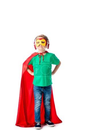Photo pour Vue pleine longueur de l'enfant d'âge préscolaire en masque et manteau héros rouge écouter de la musique dans les écouteurs et debout avec les mains sur les hanches sur blanc - image libre de droit