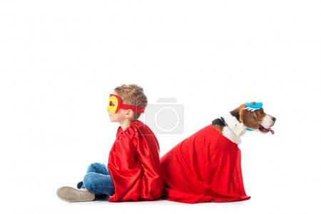Photo pour Enfant d'âge préscolaire et chien beagle dans des masques et des sabots de héros rouge assis dos à dos isolé sur blanc - image libre de droit