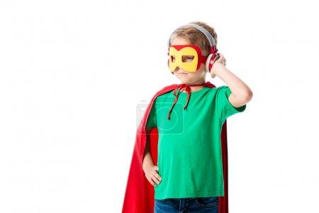 Photo pour Garçon d'âge préscolaire en manteau héros rouge et masque écouter de la musique dans les écouteurs et regarder loin isolé sur blanc - image libre de droit