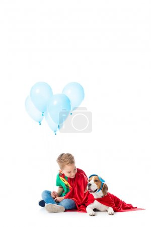 Photo for Preschooler child and beagle dog in red hero cloaks with blue party balloons on white - Royalty Free Image