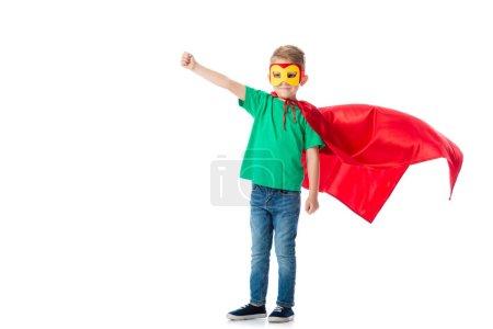 Photo pour Vue pleine longueur du garçon préscolaire souriant dans le masque et le manteau de héros rouge debout avec poing vers le haut isolé sur blanc - image libre de droit