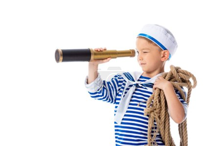 focused preschooler child in sailor costume looking in spyglass and holding rope isolated on white