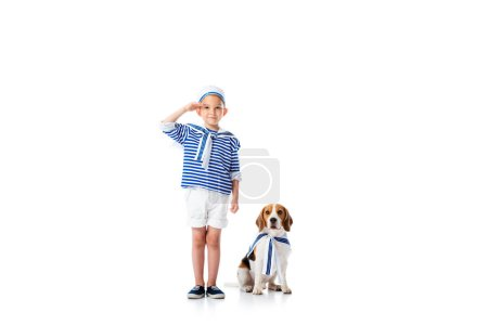 Photo for Full length view of preschooler child in sailor costume saluting with smile and beagle dog on white - Royalty Free Image
