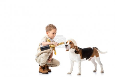 Photo for Preschooler explorer boy with spyglass and beagle dog isolated on white - Royalty Free Image
